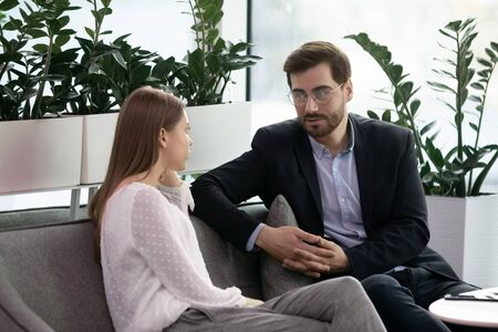 Pleasant businessman in eyeglasses resting on couch, enjoying informal conversation with young female colleague during break pause time. Coworkers communicating during workday in modern office. Stock Photo