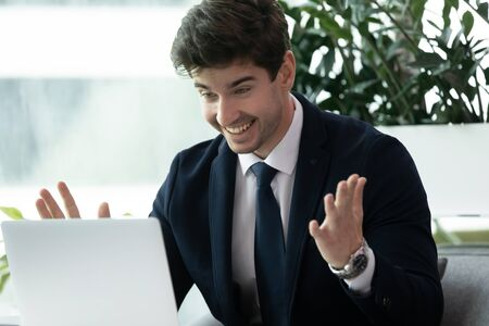 Head shot excited surprised young businessman looking at laptop screen, reading email with good news. Amazed male manager in suit getting promotion salary raising notification, working at office.