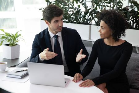 Focused young businessman in suit communicating with motivated african american female colleague in office. Pleasant biracial businesswoman listening to partners propose at brainstorming meeting.