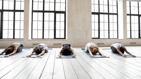 Diverse young people wearing sportswear stretching in Child pose on mats in row, practicing yoga at group lesson, doing Balasana exercise, working out, relaxing in modern yoga studio on floor