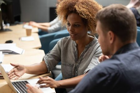 African American female employee talk cooperating with male colleagues discussing business project ideas working on laptop, ethnic woman worker speak brainstorming with coworker at coworking space Stock Photo