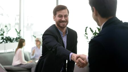 Happy businessman in eyeglasses shaking hands with partner, celebrating agreement in modern open space office. Smiling male boss lawyer agent in formal suit getting acquainted with client at meeting.