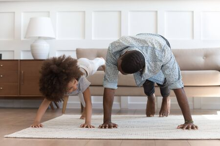 African father and small daughter in casual clothes do pushup pressup exercise on carpet on warm floor in living room, sporty lifestyle, getting physically stronger, have fun, pastime with kid concept Stock Photo