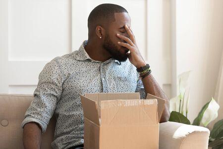 Afrykański facet siedzi na kanapie, czuje się zestresowany, zobaczył, że towar w paczce jest uszkodzony, mężczyzna z zamkniętymi oczami zakrywa twarz ręką otrzymał niewłaściwe przedmioty w paczce, niezadowolony klient, koncepcja reklamacji i zwrotu pieniędzy Zdjęcie Seryjne