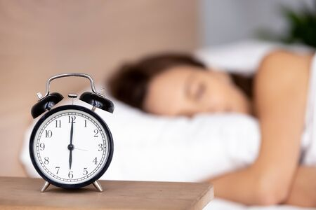 Close up of black alarm clock stand on bedside table show early morning hour, calm peaceful young woman sleep on background relax on fluffy pillow covered with warm blanket in bedroom