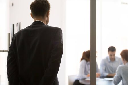 Rear view nervous man standing near glass door waiting looking at participants sitting at desk at business meeting. Lack self-confidence, public speaking fear, stressed applicant before job interview