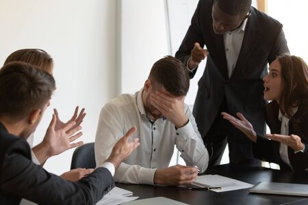 Frustrated employee cover face with hand feels unhappy having serious problems suffers from hostile co-workers, feels guilty, unfair attitude, harassment, stress, discrimination at workplace concept