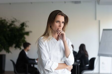 Lost in thoughts business lady entrepreneur standing in office feels concerned thinking of new challenges solving problems. Stressed woman applicant feels anxious about failed job interview concept Reklamní fotografie