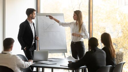 Company boss and business trainer stands in front of audience workshop participants making presentation using flip chart raised sales positive results of work done, seminar corporate education concept Stock fotó