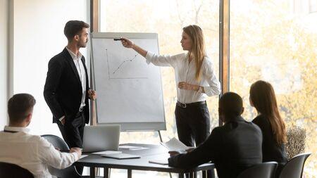 El jefe de la empresa y el capacitador de negocios se para frente a los participantes del taller de la audiencia que hacen una presentación usando un rotafolio, los resultados positivos de las ventas del trabajo realizado, el concepto de educación corporativa del seminario Foto de archivo
