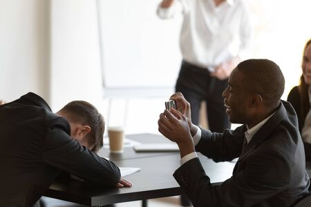 Employee sleeps sit at table put head on hands at morning briefing, african mate takes pictures of him use cellphone records video, overworked unmotivated worker, funny activity at workplace concept