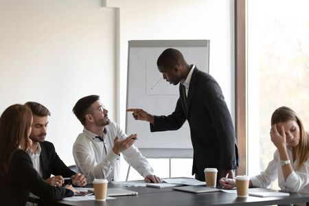 Multi-ethnic business partners having conflict accuse each other at group meeting in boardroom unpleasant situation caused by personal dislike, racial discrimination, struggle for leadership concept Stock fotó