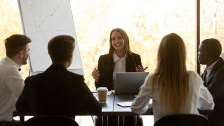 Diversos empresarios participan en reuniones grupales en la sala de juntas, los inversores escuchan a la representante de la empresa dar presentación hace oferta. El personal adquiere conocimientos en el concepto de formación corporativa del seminario Foto de archivo