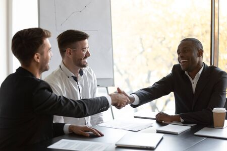 Happy African businessman shake hands with European business partner, multi-ethnic client and executive manager greeting each other seated at desk in modern boardroom starting or finishing negotiation