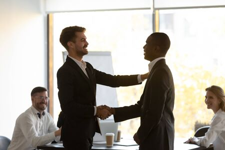 Boss praises and shake hands African member during briefing in office boardroom. Best employee of month, monetary reward for worker motivation, appreciating for good work results expresses gratitude