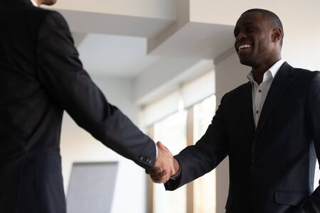 African businessman shake hands with partner express gratitude for future cooperation common business, boss praising best employee handshake showing respect congratulates with successful work concept
