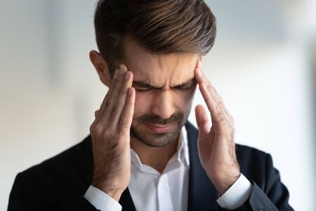 Close up of 30s businessman frown face closed eyes touches temples reduces migraine pain, feels unhealthy. Affliction caused by stressful business life, high blood pressure, need medicines concept