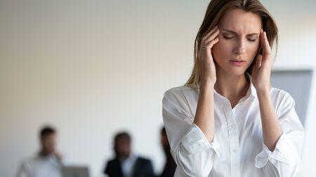 Geschäftsleute, die sich bei einem Geschäftstreffen versammelt haben, konzentrieren sich auf ungesunde 30er Jahre Frau geschlossene Augen berührt Schläfen leidet unter starken Kopfschmerzen durch Stress, Erschöpfung durch zu viel Arbeit, hormonelles Ungleichgewicht