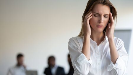 Les hommes d'affaires réunis lors d'une réunion d'affaires se concentrent sur une femme malsaine des années 30, les yeux fermés touchent les tempes souffre de forts maux de tête causés par le stress, l'épuisement par trop de travail, le déséquilibre hormonal