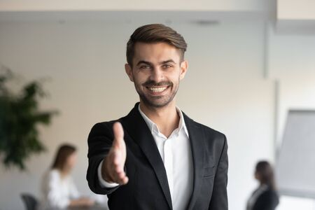 Happy businessman in suit stretch hand for handshake greet to someone, consultant extending arm at camera for hand shake, recruiter hr agent get acquainted vacancy candidature at first meeting concept Stock Photo