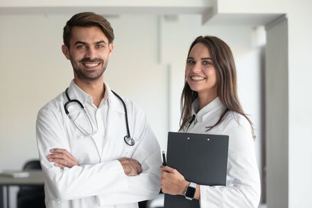 Portrait of happy Caucasian female holding clipboard and male doctor with stethoscope on shoulders wearing white coat uniform posing indoors, healthcare, medical team, successful practitioners concept
