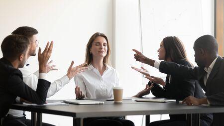 Los empresarios se sientan en el escritorio, mientras que los colegas estresados que acusan a gritos expresan emociones negativas a la joven empresaria que medita con un aspecto sereno y tranquilo, sin ansiedad por estrés en el concepto de lugar de trabajo