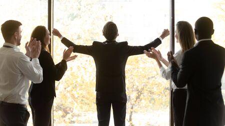 El líder del equipo feliz de la vista trasera se encuentra cerca de la ventana en la oficina y levantó las manos, se siente emocionado por la victoria del negocio. El personal corporativo aplaude mostrando respeto admirado por el talento y el éxito del concepto de colega