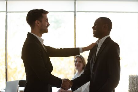 Diverse businessmen shake hand at meeting, boss appreciates leader for successful work, sales growth. Promotion best employee, motivation recognition of subordinate, support of new team member concept Stock fotó