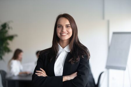 Strzał głową portret uśmiechniętej bizneswoman w eleganckim garniturze stoi z rękami skrzyżowanymi w pozie do zdjęcia w miejscu pracy, przedstawiciel młodego wykwalifikowanych specjalistów, upodmiotowienia, koncepcji przywództwa Zdjęcie Seryjne