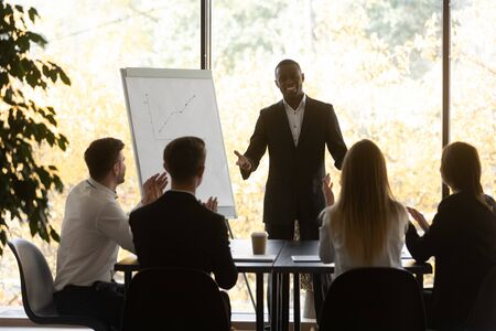 In modern boardroom gathered corporate staff, seated at desk staff members workers applaud expressing appreciation to african male speaker for successful flip chart presentation or educational seminar Stock fotó