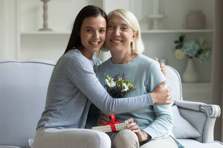 Portrait of smiling senior mother and adult daughter sit on couch look at camera celebrating birthday together, loving grownup girl congratulate happy middle-aged mom with anniversary embracing
