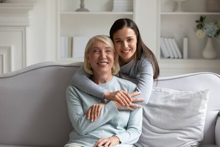 Family portrait of adult girl hug cuddle smiling middle-aged beautiful mom relaxing together on couch at home, happy grownup daughter embrace mature mother show love and care, posing look at camera 版權商用圖片