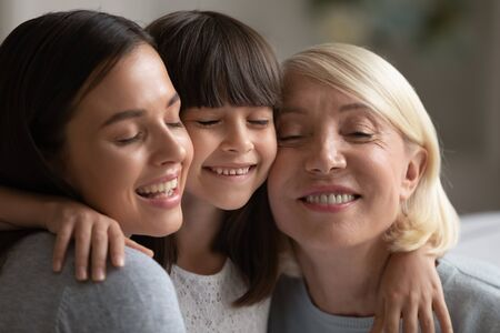 Close up of smiling three generations of women hug and cuddle having close intimate together, happy little girl, mother and grandmother embrace touch cheeks show love and care, bonding concept