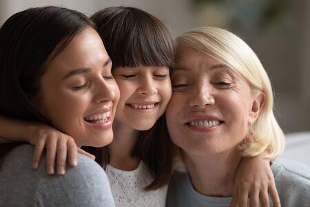 Nahaufnahme von lächelnden drei Generationen von Frauen, die sich umarmen und kuscheln, die eng miteinander intim sind, glückliches kleines Mädchen, Mutter und Großmutter umarmen Berührungswangen, zeigen Liebe und Fürsorge, Bindungskonzept