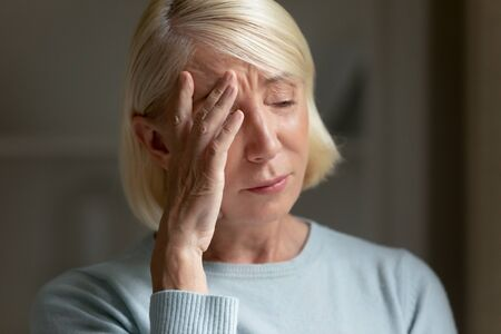Close up of upset senior woman touch head feeling down stressed crying suffering from loneliness at home, sad lonely mature female thinking and pondering struggle with elderly solitude and anxiety