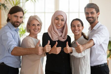 Portrait of smiling multicultural businesspeople look at camera show thumbs up give recommendation for good service, happy multiethnic diverse team posing recommend company, cooperation concept