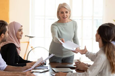 Middle-aged female coach or presenter hold meeting with multiracial employees hand share paper handout materials, mature woman leader distribute paperwork brainstorm with diverse coworkers