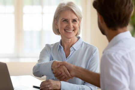 Smiling confident mature businesswoman shake hand of male business partner get acquainted or greeting at meeting, happy middle-aged female leader shake hand close deal with man coworker at briefing