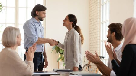 Overjoyed businessman shake hand of excited young Caucasian female employee greeting with work success or promotion, smiling colleagues shake hand get acquainted congratulate with employment Stockfoto