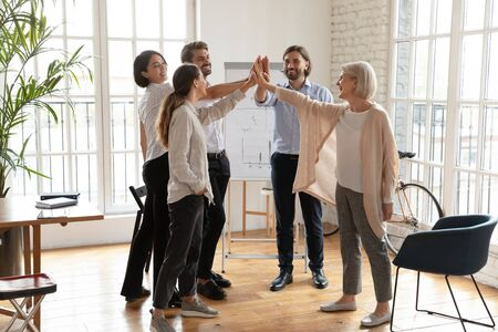 Overjoyed diverse business people stand give high five join hands celebrate shared business victory in office, happy smiling colleagues engaged in teambuilding activity at meeting, teamwork concept