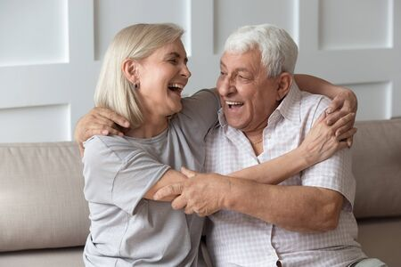 Happy mature husband and wife sit on comfortable couch have fun laughing enjoying weekend together, funny overjoyed optimistic senior spouses cuddle hug on sofa at home, elderly humor concept