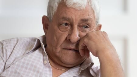 Close up of sad pensive elderly man look in distance thinking remembering good past days missing, upset thoughtful senior male feel depressed lonely pondering or mourning at home, solitude concept Stok Fotoğraf