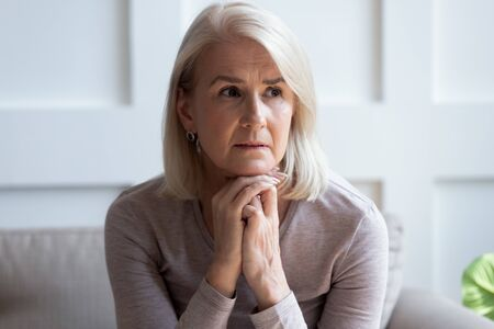 Close up of pensive upset senior woman look in distance thinking memorizing past days, thoughtful sad middle-aged mature female sit on couch lost in thoughts pondering, feel distressed mourning Stockfoto