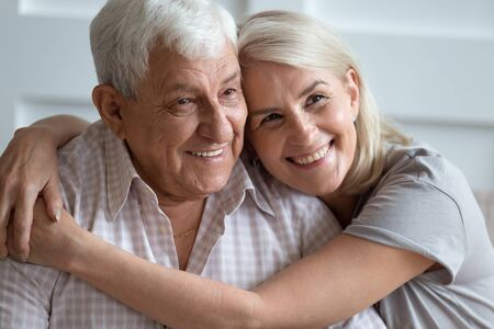 Close up headshot portrait of smiling elderly couple hug cuddle showing love and care, family picture of mature husband and wife embrace enjoy tender sweet moment on home weekend together