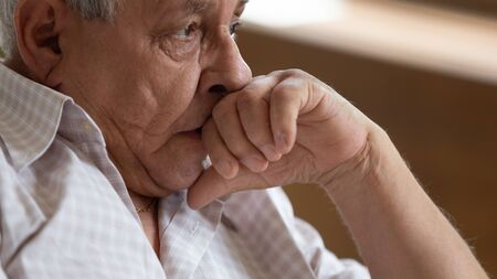 Close up of sad thoughtful lonely elderly man look in distance pondering and thinking, pensive upset senior mournful male mature grandfather lost in thoughts missing remembering, solitude concept