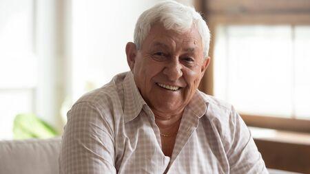 Bliska portret headshot uśmiechniętego dojrzałego mężczyzny siedzieć na kanapie w domu patrzeć na aparat pozowanie, szczęśliwy starszy mężczyzna czuje się optymistycznie podniesiony wykazać zdrowy pozytywny starszy styl życia koncepcja Zdjęcie Seryjne