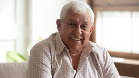 Nahaufnahme des Kopfschussporträts eines lächelnden reifen Mannes, der zu Hause auf der Couch sitzt und die Kamera posiert, glücklicher älterer Mann fühlt sich optimistisch erhoben und demonstriert ein gesundes positives Lebenskonzept für ältere Menschen Standard-Bild