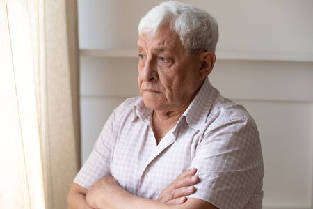 Upset old man look in window distance feel lonely and distressed thinking missing past days, thoughtful upset mature male lost in thoughts mourning yearning, remembering, elderly solitude concept