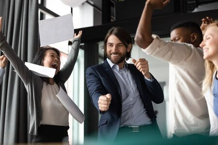 Excited diverse coworkers celebrating teamwork success together, throwing papers, Asian businesswoman screaming with joy, rejoicing business achievement, victory with colleagues in office