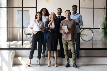 Full-length multicultural businesspeople 60s mature and millennial entrepreneurs posing together standing in modern workspace looking at camera, company personnel six successful staff portrait concept